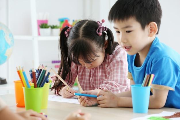 一緒にアジアの就学前の学生は色で描くことによって宿題をします