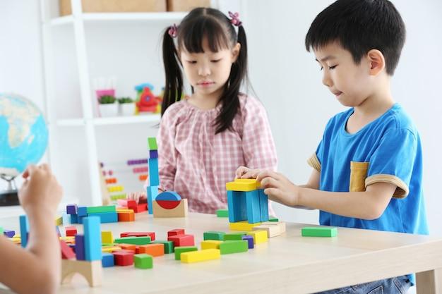 Азиатский дошкольный студент строит блок игрушки дома или детский сад. веселый малыш играет с цветные кубики. развивающие игрушки для детей дошкольного и детского сада.