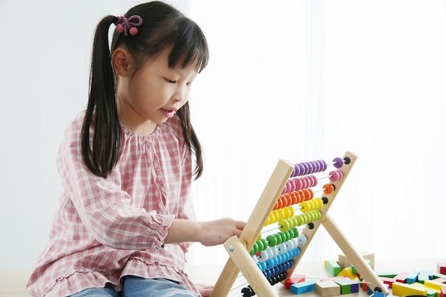 そろばんを使った幼児期の脳の発達。カラフルな木製そろばんをつかむ幼稚園児