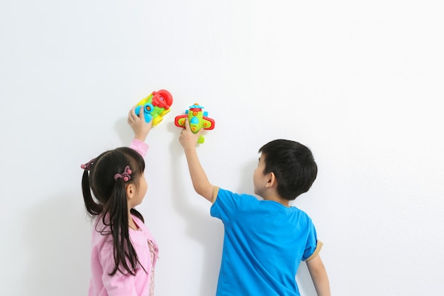 就学前の幸せな子供たちは、カラフルなプラスチックのおもちゃで遊ぶ。