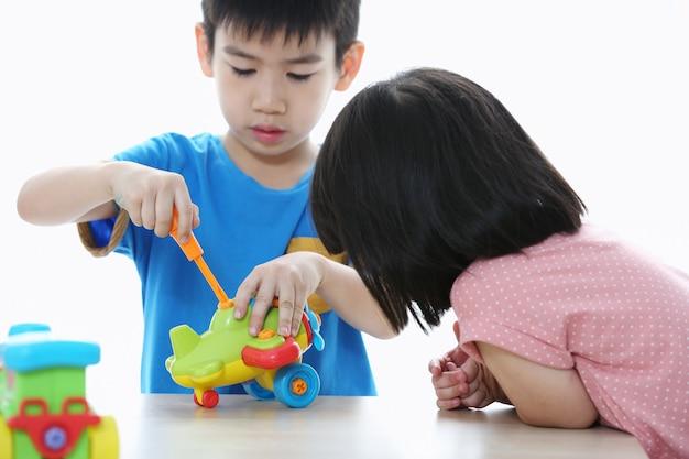 かわいい男の子と女の子はおもちゃの飛行機でサービスツールを遊んでいます。おもちゃの道具を扱う幼児。小さな職人。