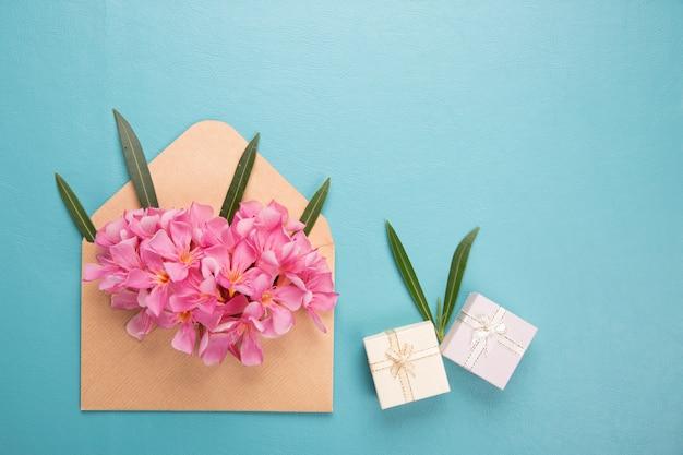 青色の背景にギフトボックスと封筒にピンクの花。
