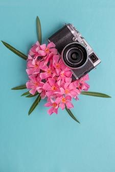 青色の背景にピンクの植物でビンテージカメラ。
