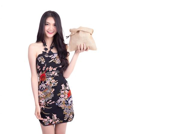 お金の受け取りを待っていると中国の旧正月に笑みを浮かべて空の袋を保持している黒いチャイナドレスを着ている美しい少女。