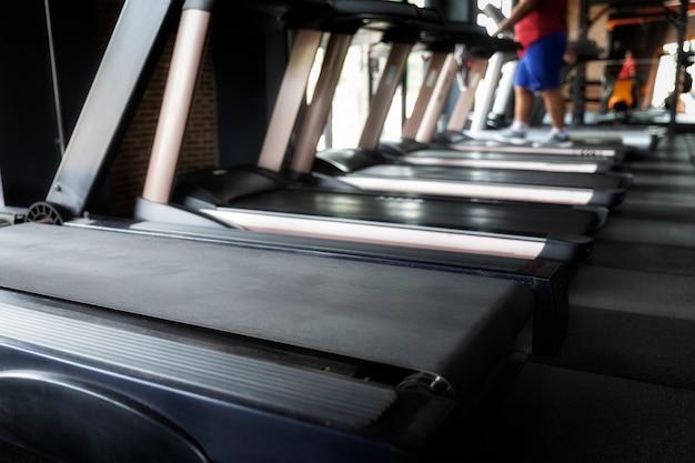 Толстяк упражнения на беговой дорожке в тренажерном зале. сосредоточены на беговой дорожке.