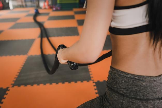 Молодая женщина работает с битвы веревки в тренажерном зале.