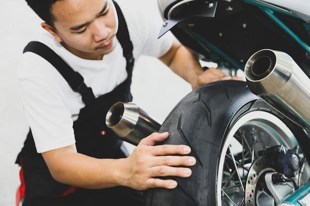 Молодой профессиональный техник ища утечку автошины мотоцикла на магазине обслуживания.