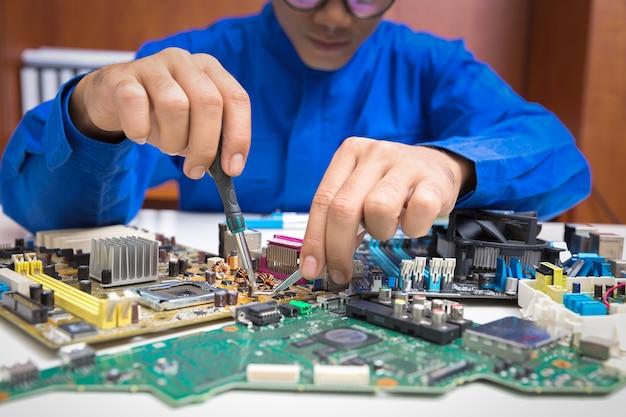 Ремонтник ремонтирует компоненты в компьютерном блоке в магазине.