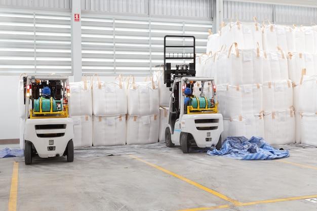 倉庫保管。倉庫の原料の大きな袋を積み上げているフォークリフトの運転手。