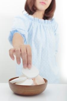 Молодая девушка, держащая косметические губки в деревянной чашке для чистки