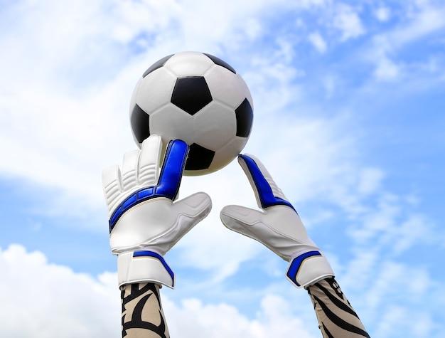 サッカーのゴールキーパーの手は、ボールのために、ネットと空を背景に到達