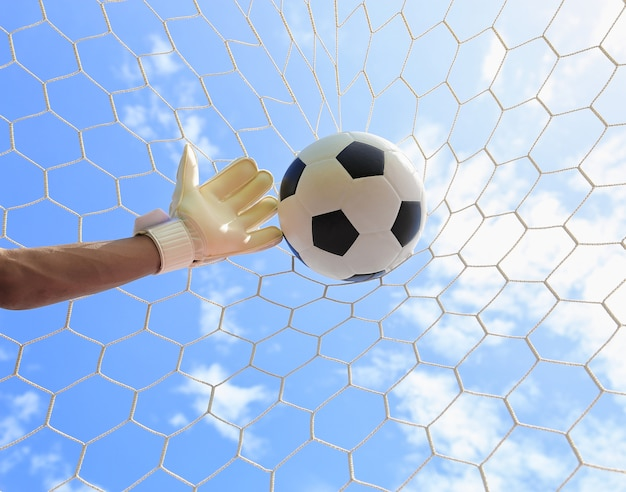 Руки футбольного вратаря тянутся к мячу, с сеткой и небом на заднем плане