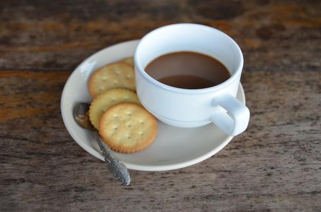 木製の背景に朝食のためのクッキーとコーヒーカップ