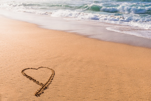 Сердце обращается в песок на пляже на закате с волнами, мыть в