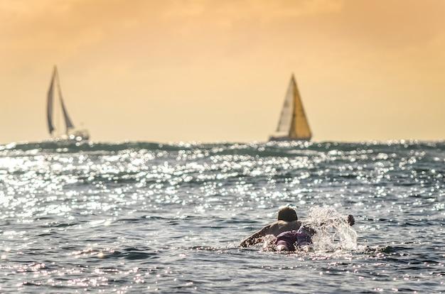 バックグラウンドでヨットとハワイの日没で漕ぐ男性サーファー