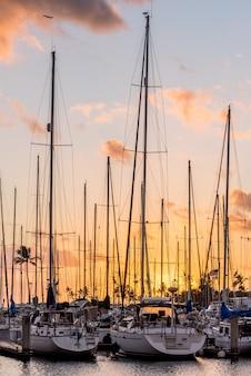 ハワイ、ホノルルのアラワイ小ボートハーバーで夕暮れ時のヨット