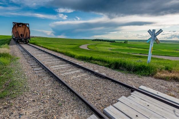 サスカチュワン州、カナダの田舎の踏切で電車の行の終わり