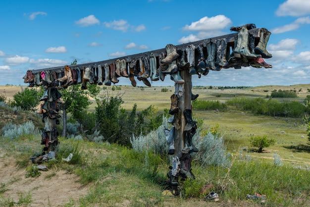 カナダ、サスカチュワン州のグレートサンドヒルズのポストに掛かっている古いカウボーイブーツ