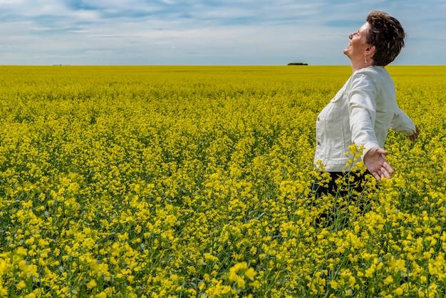 満開の菜の花畑で育った腕で立っている若い白人女性