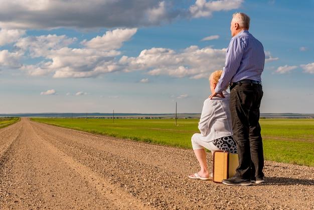 カナダの大草原の砂利道のビンテージスーツケースの上に座って年配のカップル
