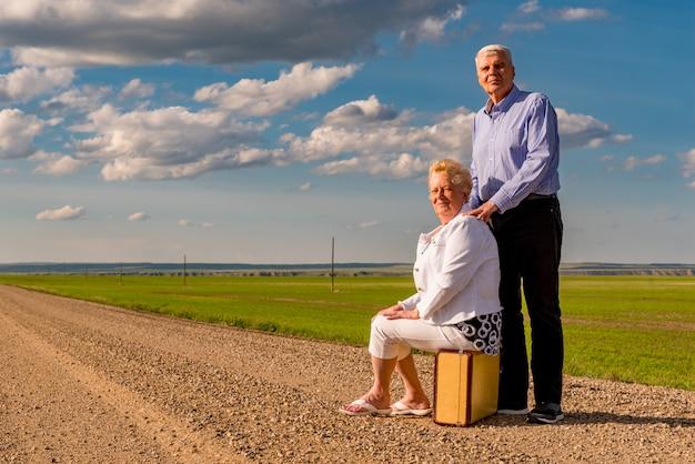 カナダ、サスカチュワン州の大草原の砂利道のビンテージスーツケースに座っている年配のカップル。冒険のコンセプト。未来のコンセプトを探しています。