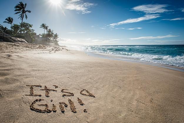 Это девушка, пол раскрывается написано в песке на сансет бич на гавайях
