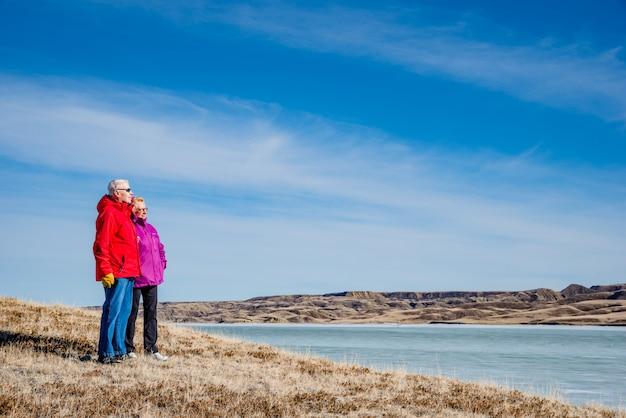 氷に覆われたディーフェンベーカー湖を見下ろす立っている年配のカップル