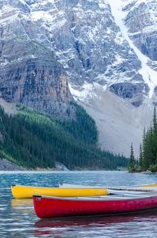 バンフ国立公園、カナダのモレイン湖の赤と黄色のカヌー