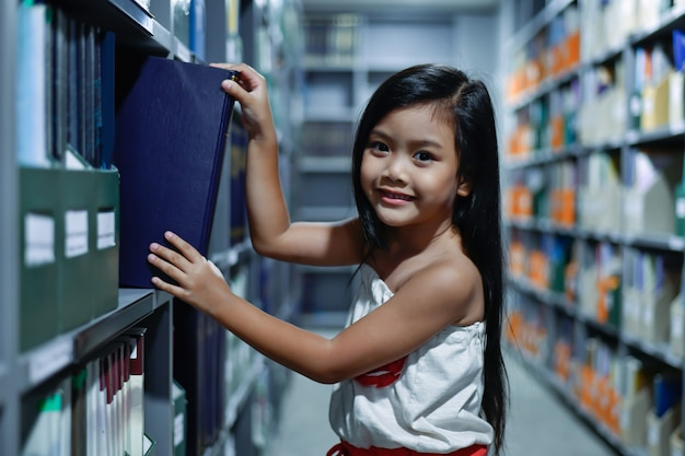 教育コンセプト。その少女は図書館で勉強しています。美しい女の子は幸せな学習です。
