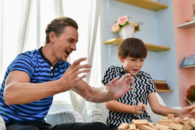 家族の概念。家族は家で幸せです。お父さんと息子は家で楽しく遊んでいます。