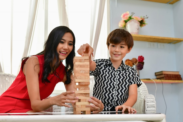 家族の概念。家族は家で幸せです。ママと息子は家で楽しく遊んでいます。