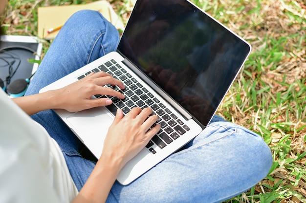 ビジネスコンセプト。ガーデンでコンピュータを演奏する女の子。