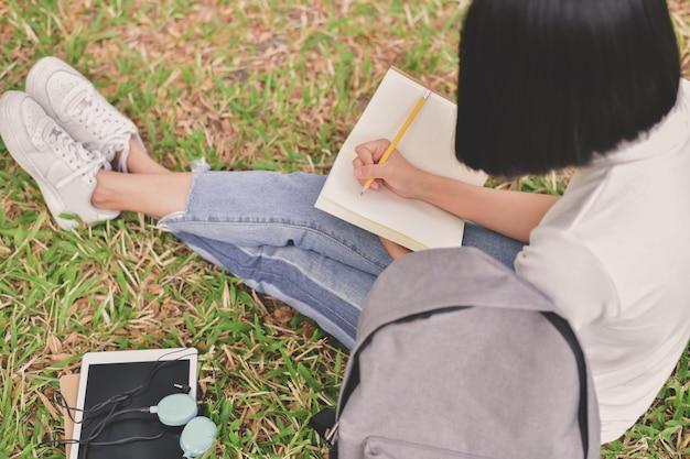 教育の概念アジアの女性が公園で本を読んでいます。