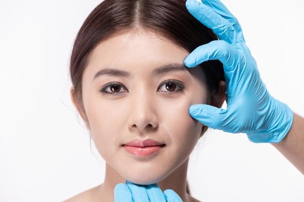 手術のコンセプトです。アジアの美しい女性が顔の手術をしています。