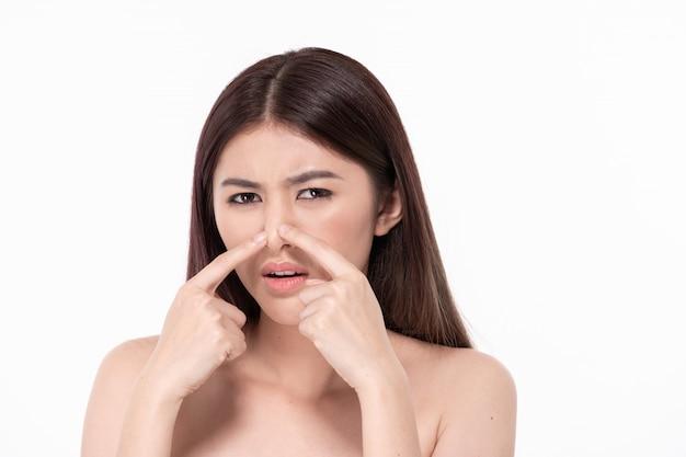 健康的な美しい女性の概念。美しい女性は肌の問題を経験しています。美しい女性が顔ににきびを絞っています。