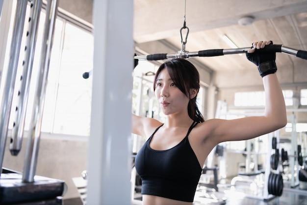 運動のコンセプトです。美しい少女がジムで運動しています。美しい少女がケーブルマシーンを弾いています。