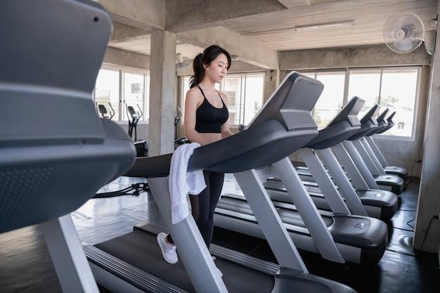 運動のコンセプトです。魅力的な若いスポーツ女性はジムでエクササイズします。トレッドミルでカーディオトレーニングをしています。
