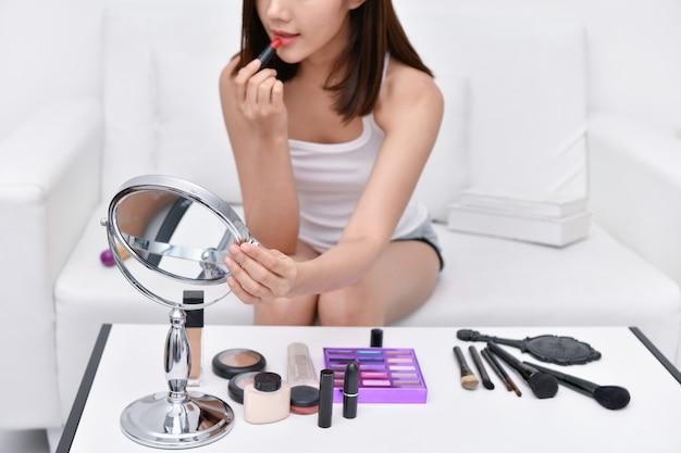 美しい少女が自宅で化粧をしています。美しい女性は自分たち自身を補うことがうれしいです。