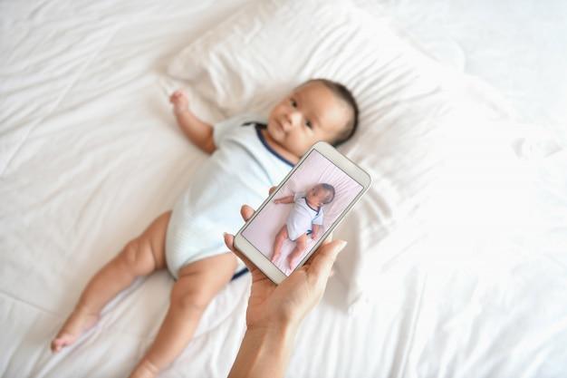 新生児のコンセプトです。母と子白いベッドの上。ママと男の子の寝室で遊んでいます。