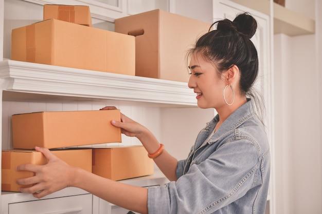 アジアの女性が自分のパッケージを梱包