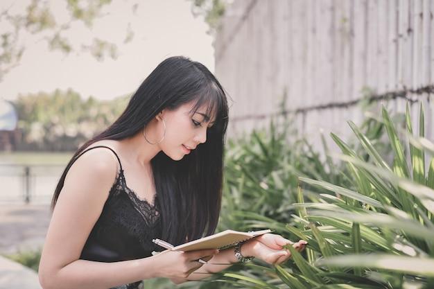アジアの女性が公園で本を読んで