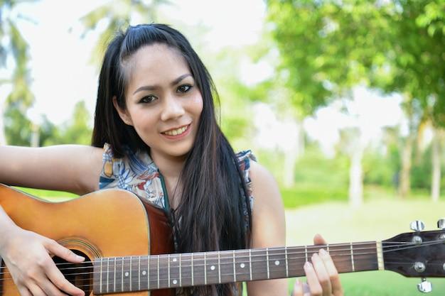 音楽のコンセプト。ギターを弾くアジアの女の子。アジアの女性は音楽でリラックスしています。