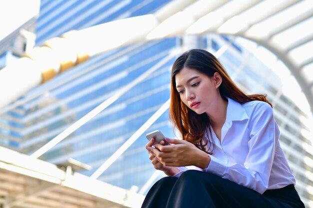 若いビジネスの女性は彼女の携帯電話で遊んでいます。
