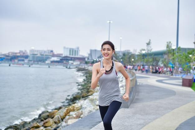 スポーツコンセプト。美しい少女が走ってビーチで運動しています。