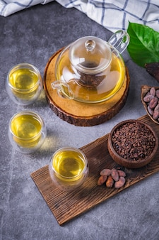 ホットカカオティー。カカオ豆フレークで作られた新鮮なホットチョコレートハーブティーは、フラボノイドと抗酸化物質が豊富で、グラスで提供されます。セレクティブフォーカス