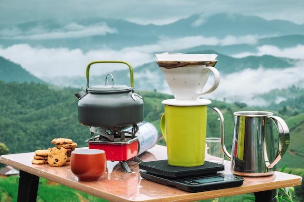 ドリップコーヒー、バリスタは、山の景色の朝にフィルターとコーヒーの地面に水を注ぐ