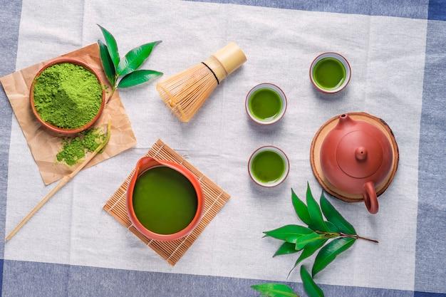 テーブルの上のセラミック皿の葉と緑茶粉末、マチャ茶道のための竹で作られた日本のワイヤー泡立て器