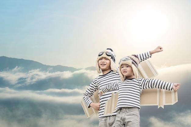 夏の空を背景におもちゃの羽で遊んで幸せな子。