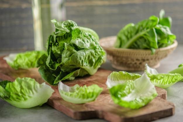 Спелый органический зеленый салат романо на разделочной доске