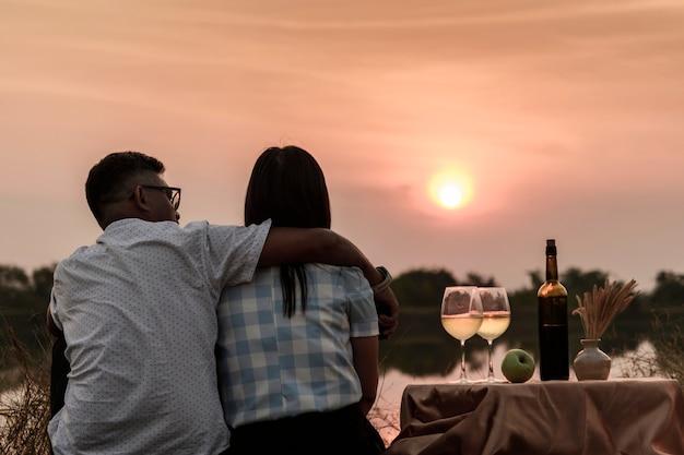 幸せな人生の瞬間。ワインを飲みながら夕日を楽しむカップル